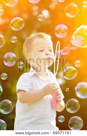 Child blowing a soap bubbles. Boy playing. Kid blowing bubbles on nature. Baby at sunset, the sun's rays