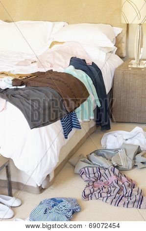 Clothes scattered on the floor and bed in the hotel room