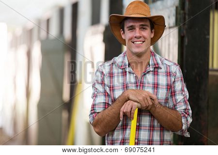 portrait of happy horse breeder inside stable