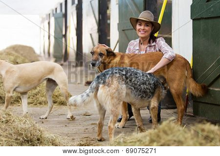 cheerful horse stables owner and dogs indoors