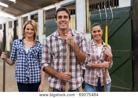 group of young stable workers with tools
