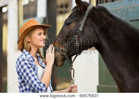 beautiful cowgirl and horse inside stable