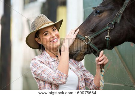 happy cowgirl and her horse in stable