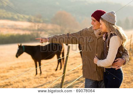 lovely young couple pointing at horse in the ranch