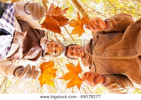underneath view of young couple holding autumn leaves in forest