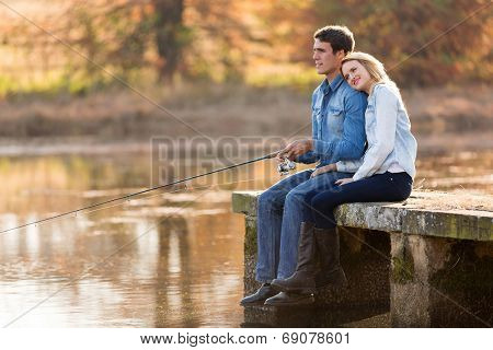 peaceful young couple fishing by the pond in autumn