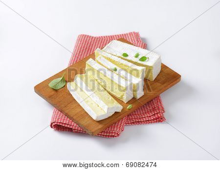 cow's milk cheese with white mold, served on the wooden cutting board with fabric linen