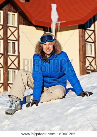 Woman Sitting On The Snow Against Hotel Building