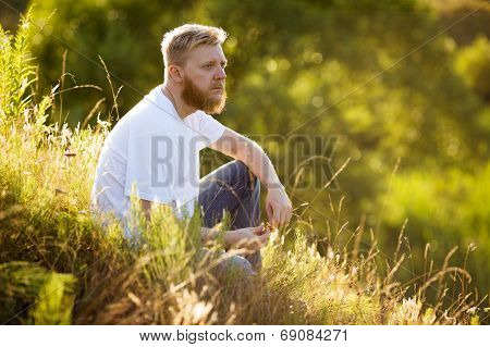 Guy Sitting On The Grass