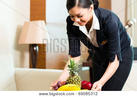 Asian Chinese hotel executive housekeeper placing fruit treatment to welcome arriving VIP guests