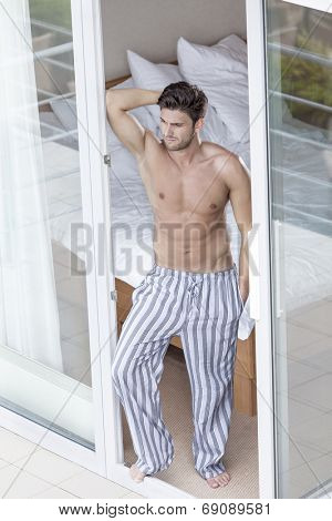 Full length of muscular young man standing at balcony doorway