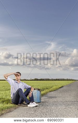 Full length of young man shielding eyes while sitting with petrol can on country road