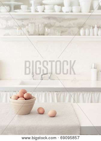 Basket of brown eggs on countertop with bowls on shelf in white kitchen