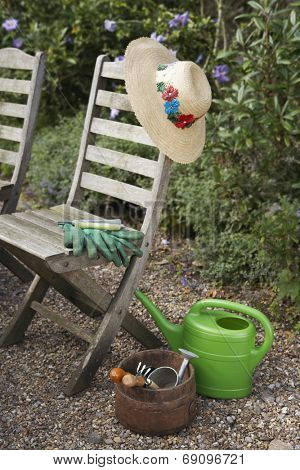 Closeup of gardening tools and chairs in the garden