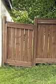 picture of sag  - A sagging wooden gate over a grass area with trees behind - JPG