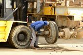stock photo of scrap-iron  - Worker removing a tire from a old steel industrial trailer prior to metal recycling at a scrap yard - JPG