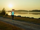 picture of early morning  - Sporty fitness woman runs in the park early in the morning sunrise on the background - JPG
