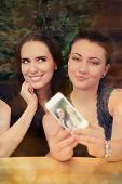 image of two women taking cell phone  - Two girls taking a funny photo together with their smart phone - JPG