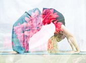 stock photo of dhanurasana  - Double exposure portrait of young woman performing back bend combined with photograph of nature - JPG