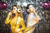 stock photo of catsuit  - two beautiful sexy disco women in gold and silver catsuits dancing in a club setting - JPG
