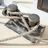 pic of bollard  - Dark bollard with rope knot on yacht deck