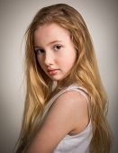 pic of shy girl  - Portrait of a beautiful young girl with long blond hair and bare shoulders isolated against a grey background - JPG