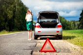 picture of warning-signs  - Close up on triangle warning sign with woman calling for assistance after breaking down with her car on background