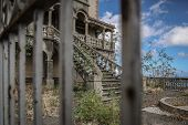 stock photo of old stone fence  - Abandoned Villa viewed through a metal fence looking at a small yard with an old pool an a stairway - JPG
