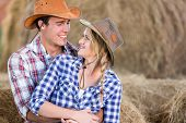 stock photo of barn house  - loving young american western couple hugging in barn - JPG