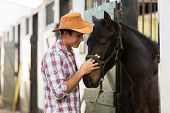 picture of stable horse  - young horse breeder comforting a horse in stable - JPG