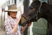 stock photo of working animal  - caring cowgirl talking to a horse in farm house - JPG