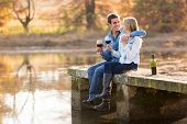 picture of snuggle  - happy young couple drinking red wine by the lake - JPG