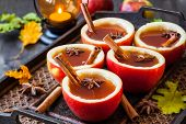 picture of christmas spices  - Apple cider with cinnamon sticks and anise star in apple cups - JPG
