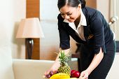 stock photo of housekeeping  - Asian Chinese hotel executive housekeeper placing fruit treatment to welcome arriving VIP guests - JPG