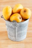 foto of loquat  - loquat fruit in bucket on wooden table - JPG