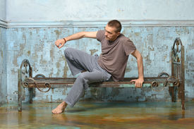pic of scourge  - Man on the metal rusty bed in prison - JPG