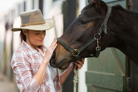 image of cowgirl  - caring cowgirl talking to a horse in farm house - JPG