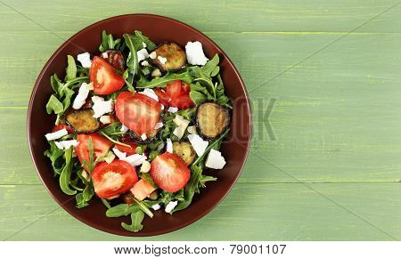 Eggplant salad with tomatoes, arugula and feta cheese, on wooden background
