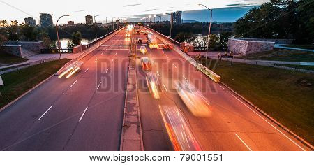 Streams of cars and trucks driving over a bridge at night.