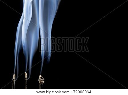 delicate smoke plumes from burning incense sticks with a copy space