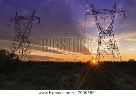 Electrical power transmission towers over the desert in Arizona at Sunset