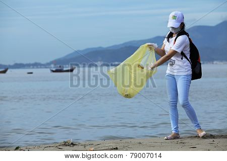 A student of Nha Trang University cleaning the beach within a volunteer event