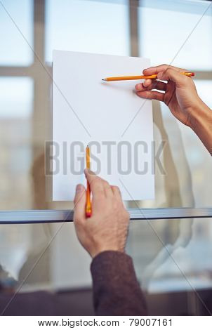 Male hand with pencil pointing at blank paper on noticeboard