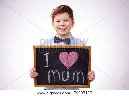 Adorable boy holding board with declaration of love to his mother