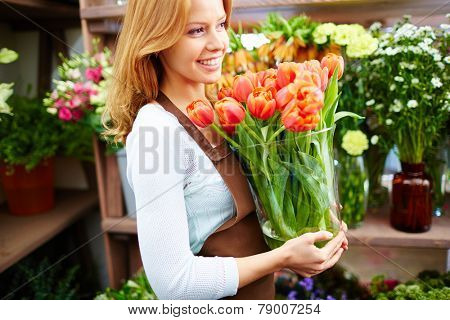 Young florist or gardener holding red tulips in glassware