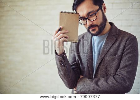 Young businessman with notepad thinking in office