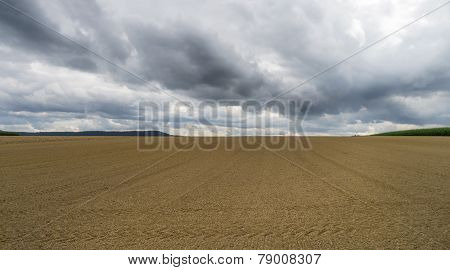 Harrowed field with dark clouds