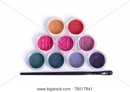Top view of mineral eye shadows and brush, isolated on white background with natural shadow