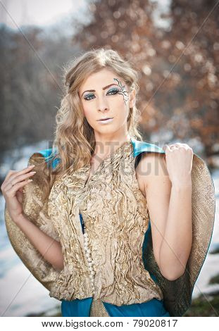Lovely young lady in elegant dress posing winter scenery, royal look. Fashionable blonde woman