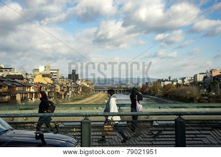 KYOTO, JAPAN - DECEMBER 03, 2014: Pedestrians cross the bridge walking towards Kyoto, Japan on the way to work on a winter morning. Kyoto is the old capital of Japan and still a thriving city today.